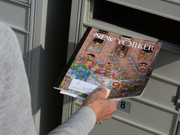 A woman retrieves a copy of <em>The New Yorker</em> magazine from her mailbox in Santa Fe, N.M., in 2020.