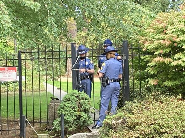Washington State Patrol troopers use a chain to secure a gate at the governor's residence following a security breach on Wednesday, September 15, 2021.