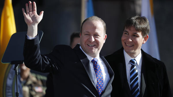 Colorado Gov. Jared Polis, left, waves to the crowd accompanied by his partner, Marlon Reis, in 2019. The two were married Wednesday, marking the first same-sex marriage of a sitting governor.