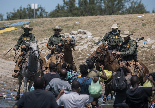 U.S. Customs and Border Protection mounted officers attempt to contain migrants as they cross the Rio Grande from Ciudad Acuña, Mexico, into Del Rio, Texas, on Sunday