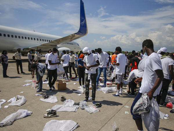 Haitians deported from the U.S. recover their belongings scattered on the tarmac of the Toussaint Louverture International Airport on Tuesday in Port-au-Prince, Haiti.