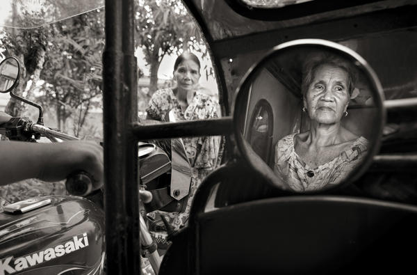 """Isabelita Vinuya, 88, reflected in mirror, bids farewell to Perla Bulaon Balingit in the village of Mapaniqui in Pampanga. They are two of the last living """"comfort women"""" of the Philippines. On Nov. 23, 1944, Vinuya, Balingit and some 100 other girls and women were taken to the Red House and systematically raped by the Japanese Imperial Army."""