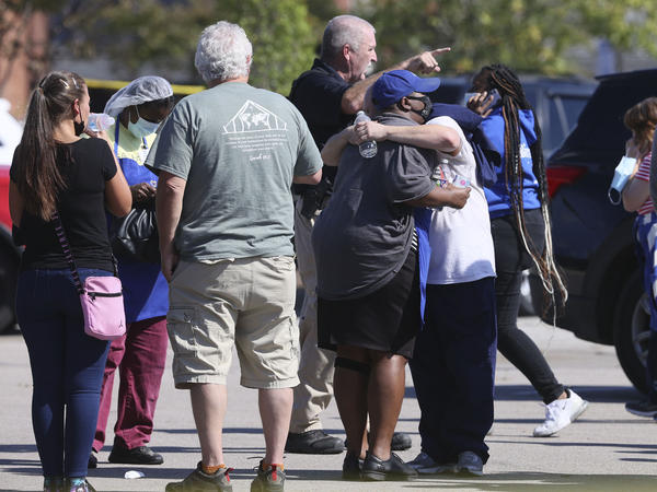 People embrace as police respond to the scene of a shooting at a Kroger grocery store in Collierville, Tenn., on Thursday. Police say 13 people were injured, one of whom has died. The suspected shooter also died from what police say was a self-inflicted gunshot wound.