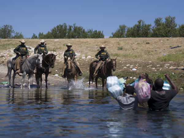U.S. Border Patrol agents on horseback block migrants crossing the Rio Grande on Sunday near the Del Rio-Acuña Port of Entry in Texas. Horse patrols at that part of the border have been suspended, the White House press secretary says.