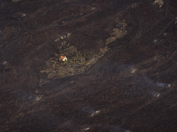 Lava from a volcanic eruption surrounds a house on the island of La Palma in the Canary Islands on Thursday.