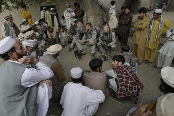 An American lieutenant, center, meets with villagers in Afghanistan's Kunar province in 2009, assisted by an interpreter, sitting to his right wearing a baseball cap. The U.S. will begin the evacuation of some 18,000 Afghan nationals who aided military operations, along with their families, in late July.
