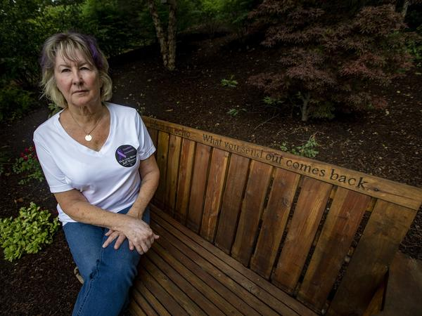 Lynn Wencus sits on a bench in her backyard dedicated to her son Jeff, whom she lost to an opioid overdose in 2017. She is one of many people filing an individual claim in the Purdue Pharma settlement.