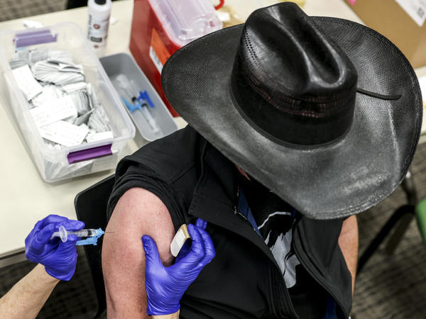 Colorado's UCHealth hospital system is requiring any prospective organ transplant recipients to get the COVID-19 vaccine. Here, a man receives a COVID-19 vaccine in Thornton, Colo., earlier this year.