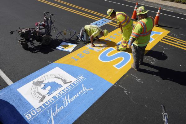 Painter Will Belezos, of Holbrook, left, uses a stencil, Wednesday, Oct 6, 2021, while working to complete the start line for the 125th edition of the Boston Marathon, in Hopkinton. (Steven Senne/AP)