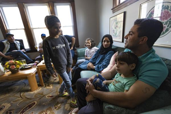The Atayi family gathers with cousins and new friends two days after moving into their apartment in Worcester. They fled Afghanistan after the Taliban took control. (Jesse Costa/WBUR)
