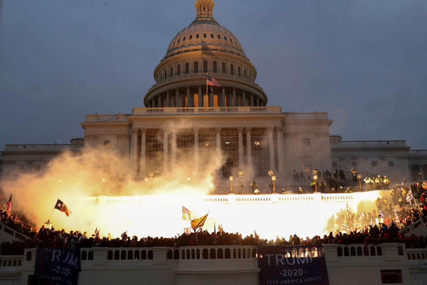 An explosion caused by a police munition is seen while supporters of then-President Donald Trump gather in front of the U.S. Capitol in Washington, D.C., on Jan. 6.