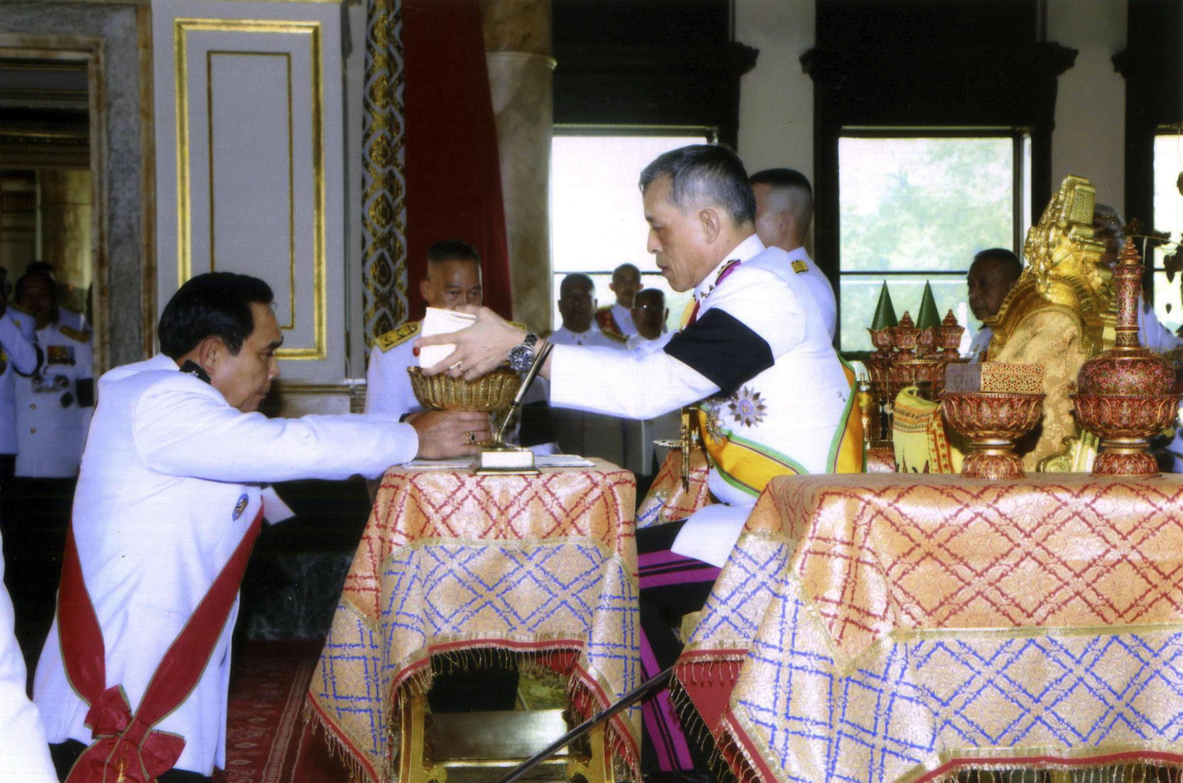 El Rey Vajiralongkorn Bodindradebayavarangkun (derecha) firma la nueva constitución de la junta durante la ceremonia junto al Primer Ministro y líder de la junta Prayuth Chan-ocha (izquierda) | Fuente: Associated Press
