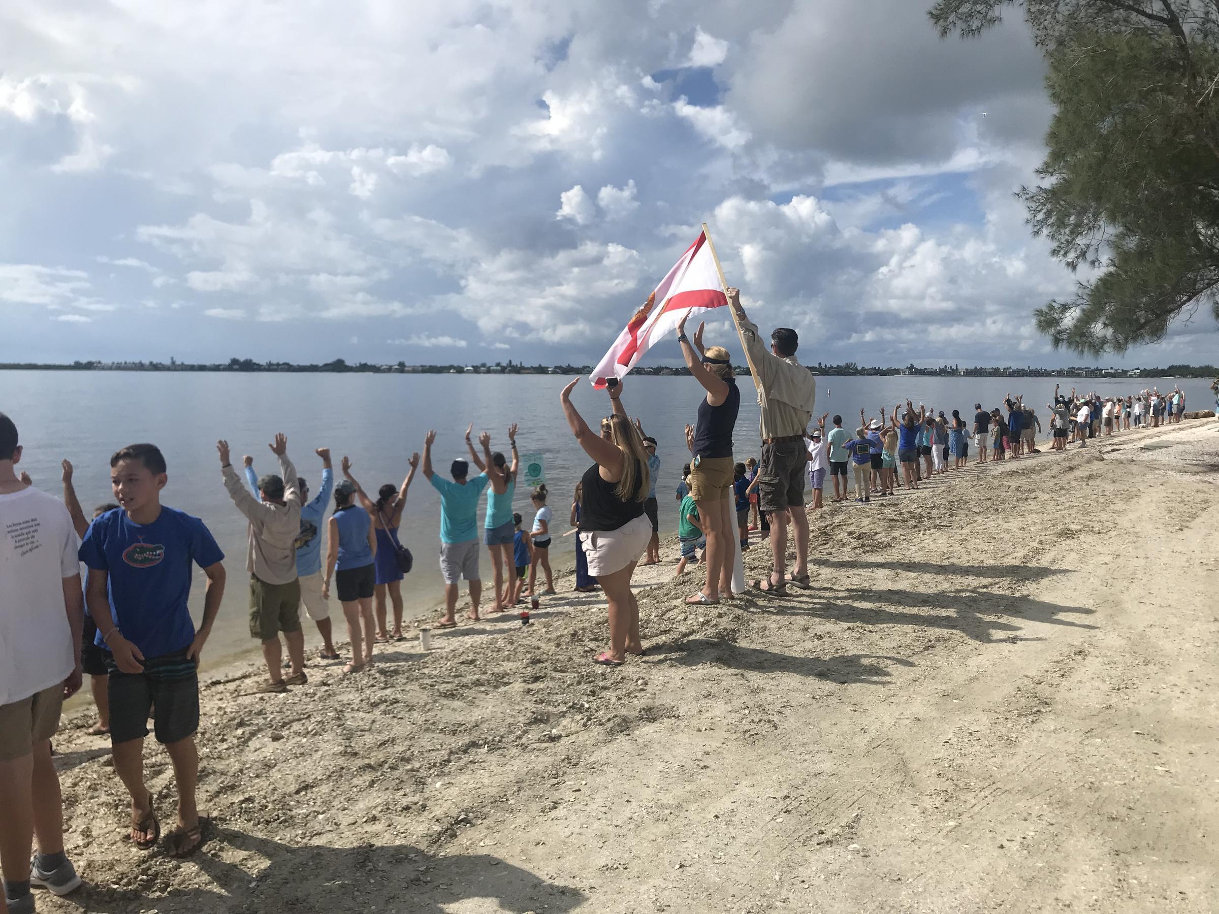 Demonstrators Raise Their Hands As Part Of A Along The Water Event Sanibel Causeway