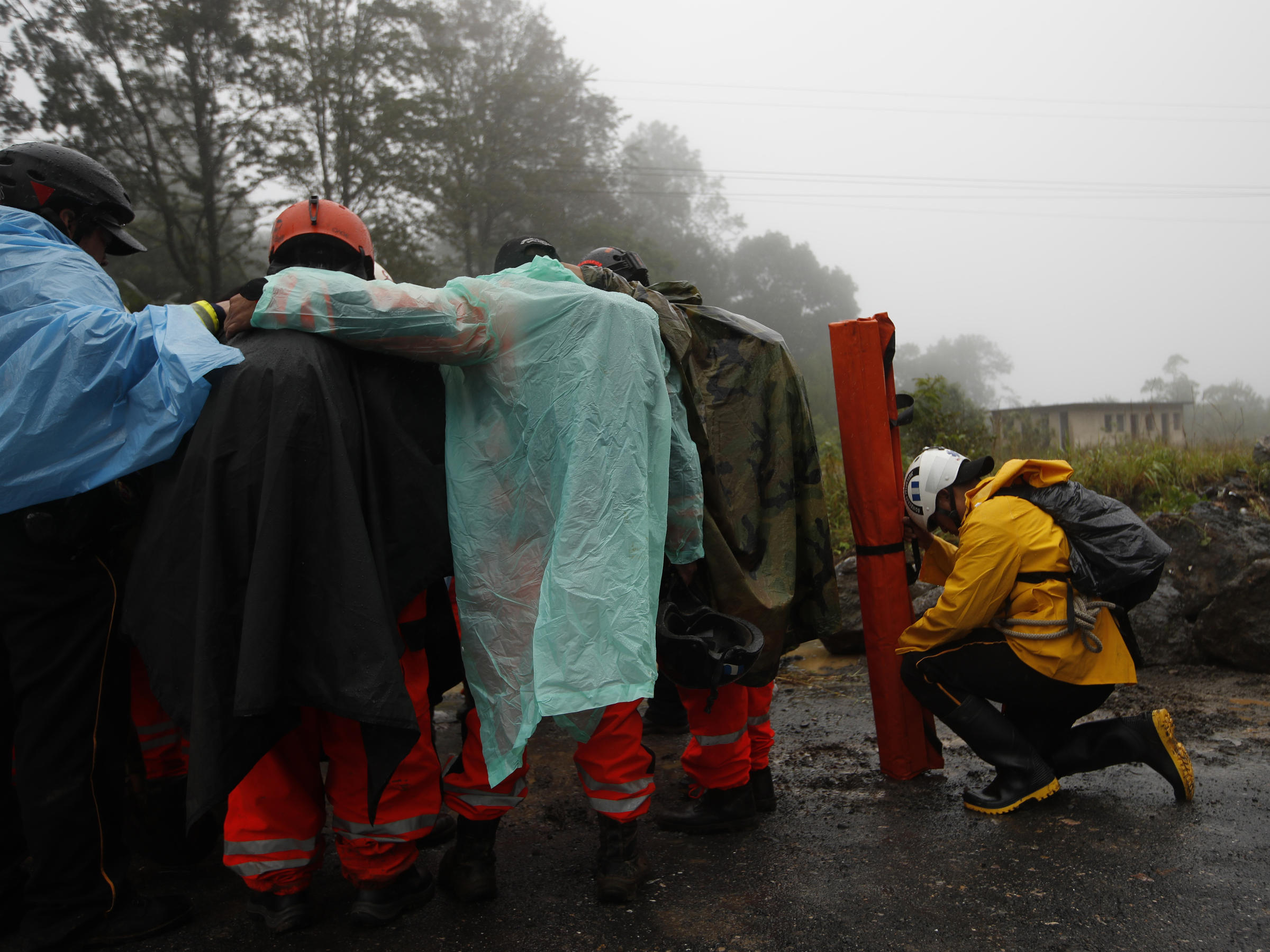 Volunteer firefighters huddle in prayer before beginning a search and rescue operation Nov. 7 in San Cristóbal Verapaz Guatemala in the aftermath of Hurricane Eta