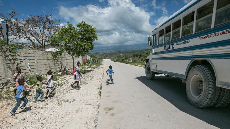 <p>Migrant children board a bus outside the Notre Dame de Lourdes School in Anse-a-Pitres, Haiti, to return to their shelters after morning classes.</p>