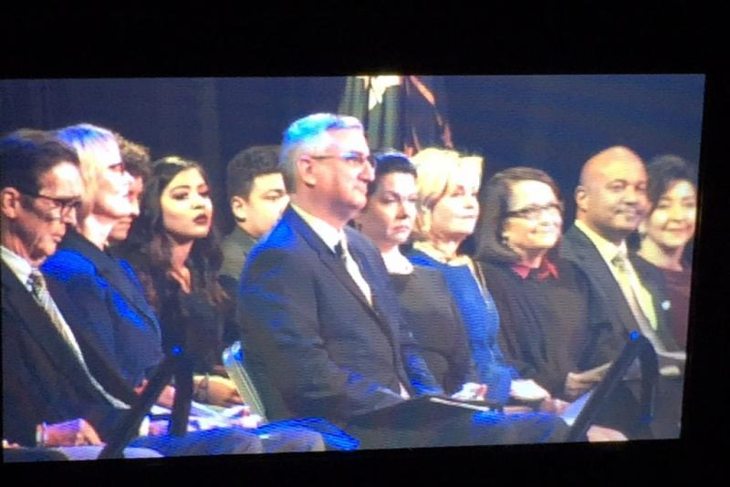 Governor Eric Holcomb, as seen through the viewfinder of a TV camera, sits on stage at the Indiana Coliseum at the State Fairgrounds during his inauguration. (Brandon Smith/IPB News)