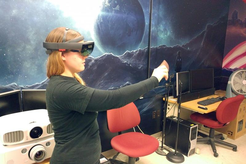Purdue University senior Jordyn Lukomski uses her finger and a Microsoft HoloLens to navigate an augmented reality grasshopper dissection simulation she and her classmates built. (Annie Ropeik/IPB News)