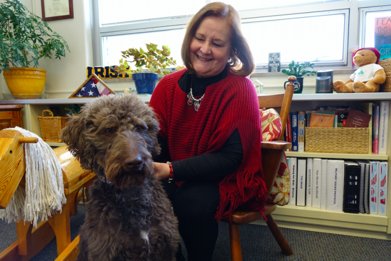 Rebecca Heger, Cathedral High School's mental health and addictions counselor, looks at 2-year-old Finn, a therapy dog at the school since 2015. (Credit: Eric Weddle)