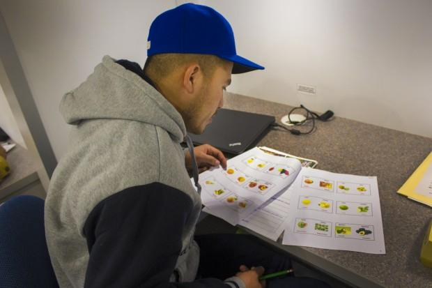 A student studies a sheet with fruits and vegetables in the Indiana Region 4 migrant education center's mobile classroom. (Peter Balonon-Rosen/IPB News)