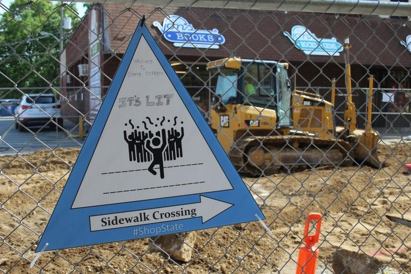 A sign telling pedestrians how to cross construction to access local businesses got some original artwork along West Lafayette's State Street. (Annie Ropeik/IPB News)