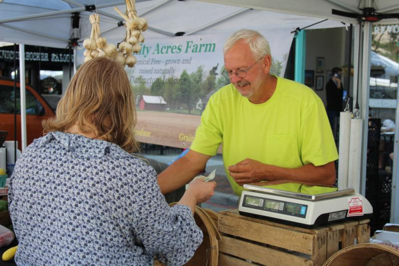Montgomery County-based grower Gary Cox makes change for a customer in his Trinity Acres Farm tent at the Lafayette Farmers Market. (Annie Ropeik/IPB News)