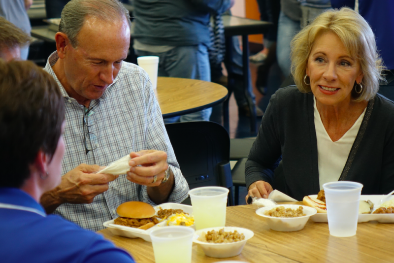 "U.S. Education Secretary Betsy DeVos and husband Dick eat at the Eastern Hancock High School cafeteria for the annual FFA hog roast fundraiser on Friday, Sept. 15, 2017 during the last stop on the ""Rethink School"" tour. (Credit: Eric Weddle/WFYI News)"