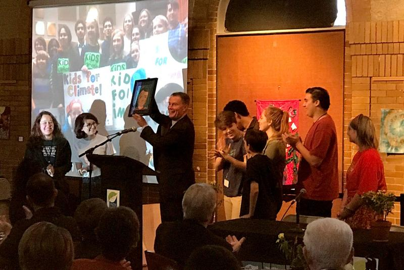Indianapolis Mayor Joe Hogsett accepts a gift from Cora Gordon (clapping, right) and other members of Youth Power Indiana, which pushed for a city-county climate resolution earlier this year. (Nick Janzen/IPB News)