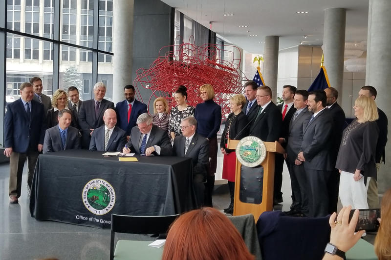 Gov. Eric Holcomb signs workforce bills with Indiana lawmakers and other state lawmakers and business leaders. (Samantha Horton/IPB News)