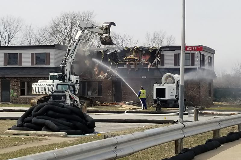 Crews begin tearing down a portion of the West Calumet Housing Complex on April 2. They drench the debris to prevent the spread of lead and arsenic contamination to the surrounding neighborhood. (Lauren Chapman/IPB News)