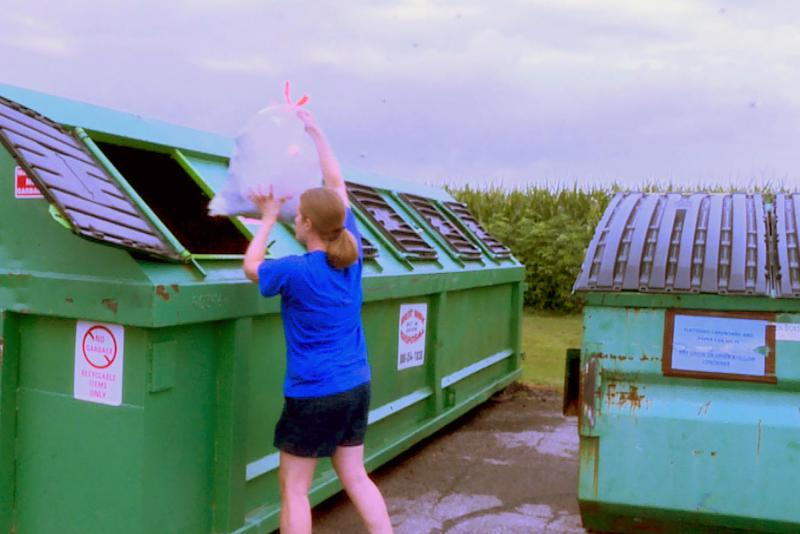 Amy Rather drops recycling into one of the bins behind the Johnson County Recycling District office. After July 31, this bin won't be available. (Rebecca Thiele/IPB News)
