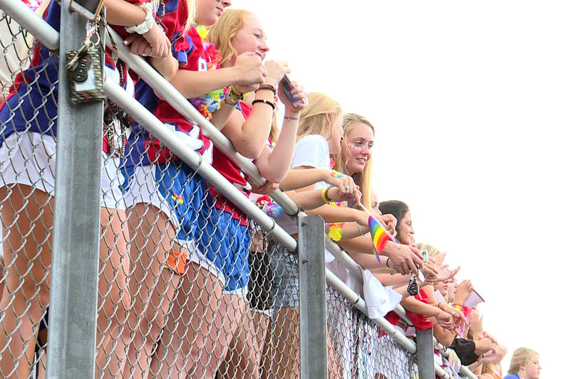 Roncalli students wave rainbow flags during their first football game of the season in support of Shelly Fitzgerald, a guidance counselor whose job has been threatened because of her marriage to a woman. (Lauren Chapman/IPB News)