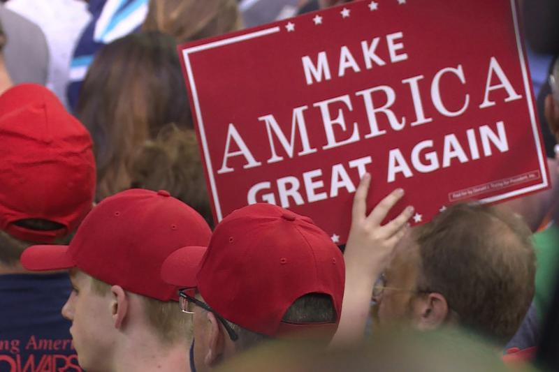 Trump supporters inside the Ford Center in Evansville hold signs during the president's speech. (Alex Eady/WTIU)