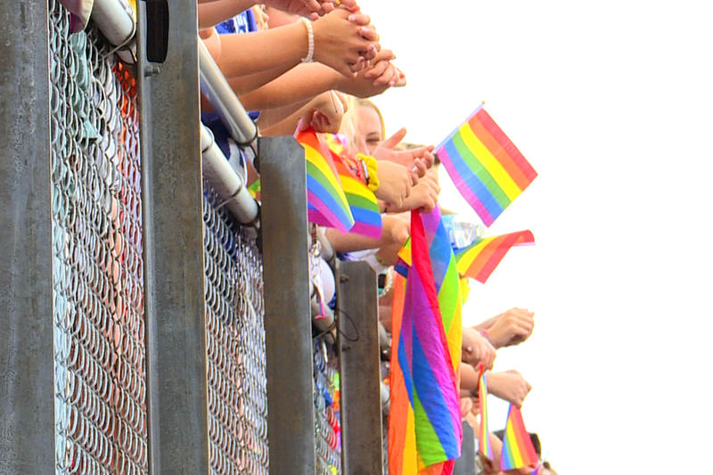 Students at a Roncalli football game wave rainbow flags to support counselor Shelley Fitzgerald. State Superintendent Jennifer McCormick says the situation brought attention to voucher schools with discriminatory practices. (Lauren Chapman/IPB News)