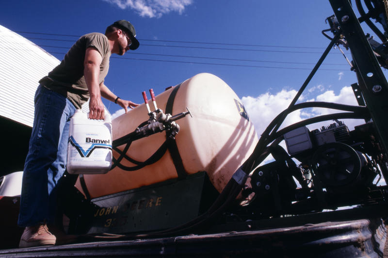 An old photo of a man filling a sprayer tank with Banvel, a brand name for dicamba herbicide in 1985. (USDA NRCS)