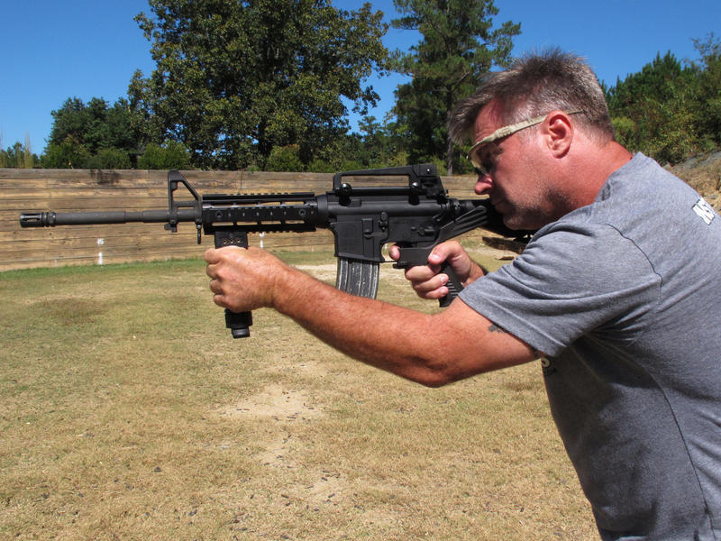 """Shooting instructor Frankie McRae aims an AR-15 rifle fitted with a """"bump stock"""" that allows the semi-automatic to shoot as fast as an illegal machine gun. As of March 26, bump stocks will be effectively illegal to own unless a court puts an injunction on"""