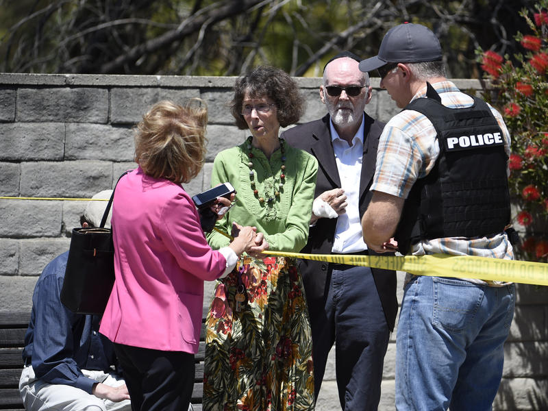 Synagogue members talk to a San Diego County Sheriff's deputy outside of the Chabad of Poway Synagogue on Saturday in Poway, Calif.