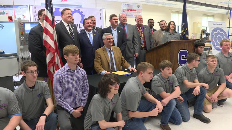 Gov. Eric Holcomb and legislators pose with students at Seymour High School after signing a career and technical education bill into law. (Zachary Herndon/WTIU)