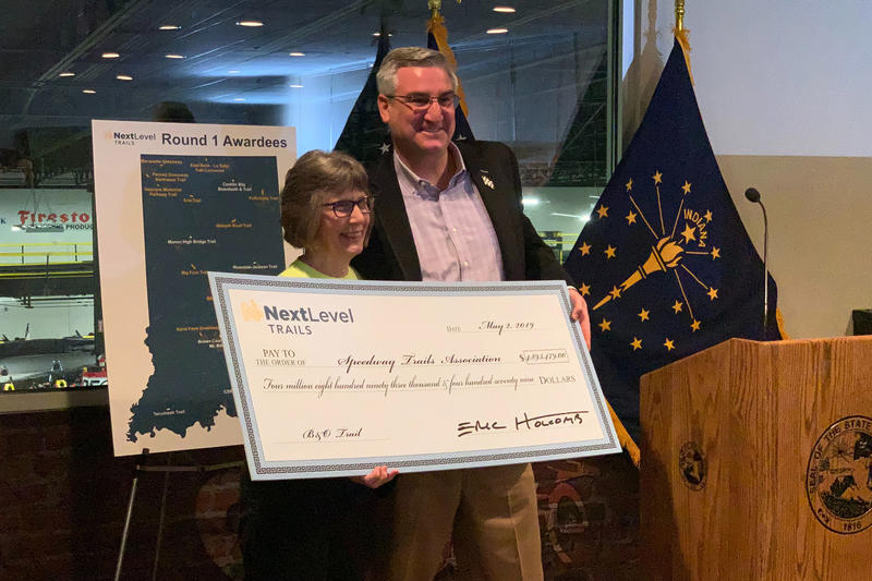 Gov. Eric Holcomb poses with the head of the Speedway Trails Association, which received the single largest award from the first round of the Next Level Trails program. (Brandon Smith/IPB News)