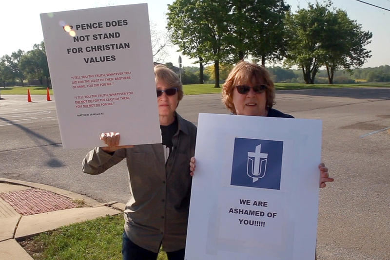 Christine Newman-Aumiller, right, and her sister, Marilyn Dodds, protested outside the commencement address. Both are Taylor alumna who say they are disappointed in the school's decision to have Pence speak. (Aric Harvig/IPB News)