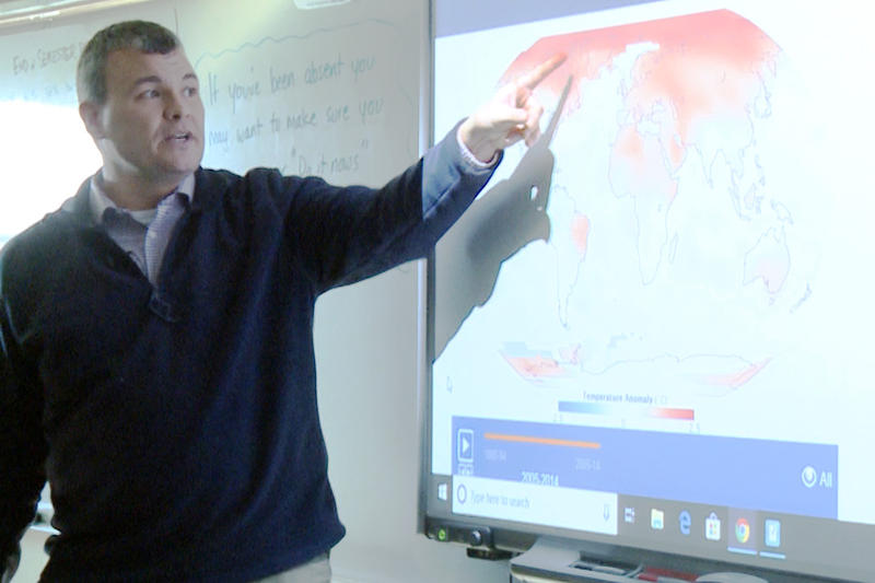 Keith Morey at Centerville-Abington Junior High points to an animated NASA map showing how average temperatures have changed since the late 1800s (Tyler Lake, WTIU)