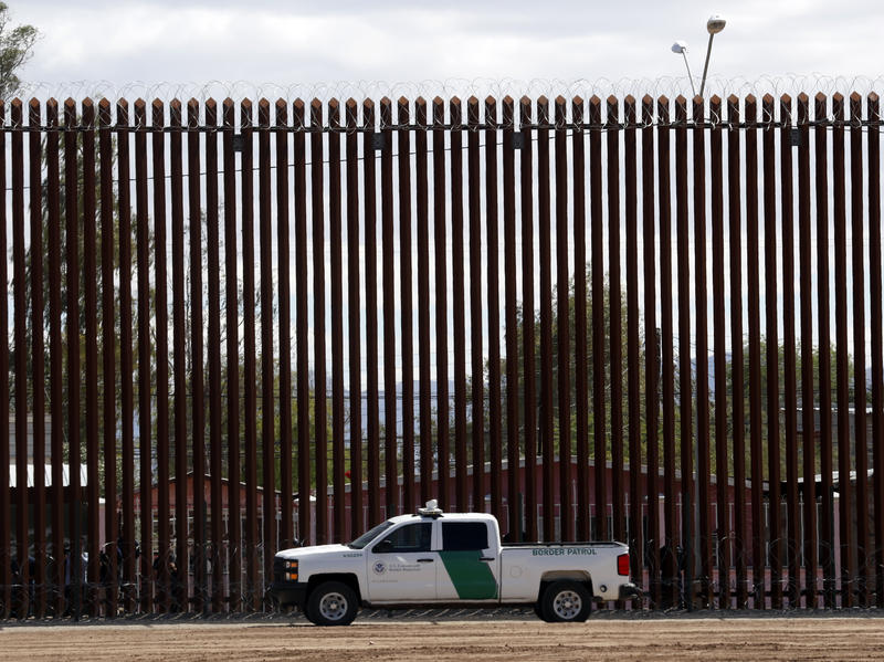 A U.S. Customs and Border Protection vehicle sits near the wall as President Donald Trump visits a new section of the border wall with Mexico in El Centro, Calif., on April 5. This area is one where the Pentagon will spend more resources shifted away from