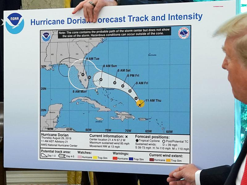 President Trump in the Oval Office references a map showing Hurricane Dorian's path. The map appears to have been altered by a black marker to extend the hurricane's range to Alabama.