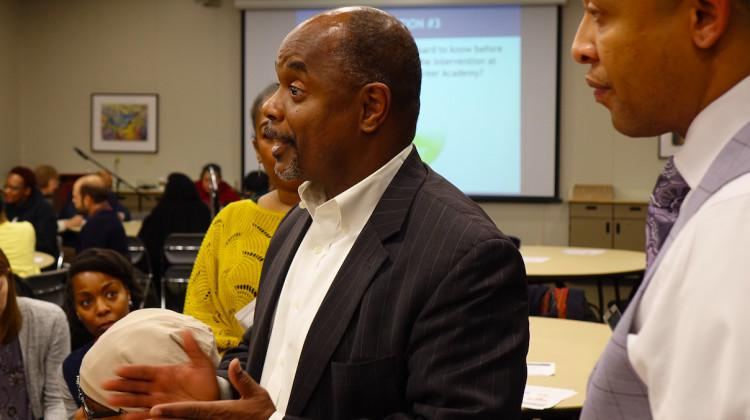 Thom Jackson, CEO of Florida-based Edison Learning, left, talks to Gary community members as Roosevelt principal Joshua Batchelor, right, listens during a public hearing Monday, Dec. 16, 2019.