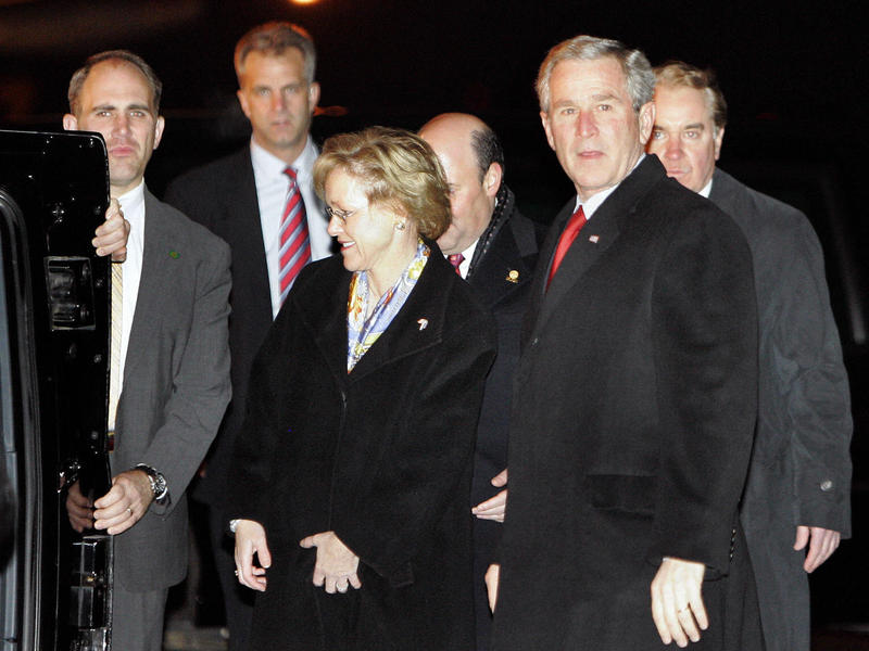 Former President George W. Bush stands beside then-U.S. Ambassador to Estonia Aldona Wos, wife of current Postmaster General Louis DeJoy, upon Bush's arrival on Nov. 27, 2006, at the airport in Tallinn, Estonia.