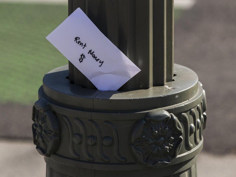 """An envelope labeled """"Rent Money"""" is left tucked in a lighting pole in Los Angeles on April 1. President Trump's new executive order to prevent evictions isn't enough and Congress needs to act, housing activists say."""