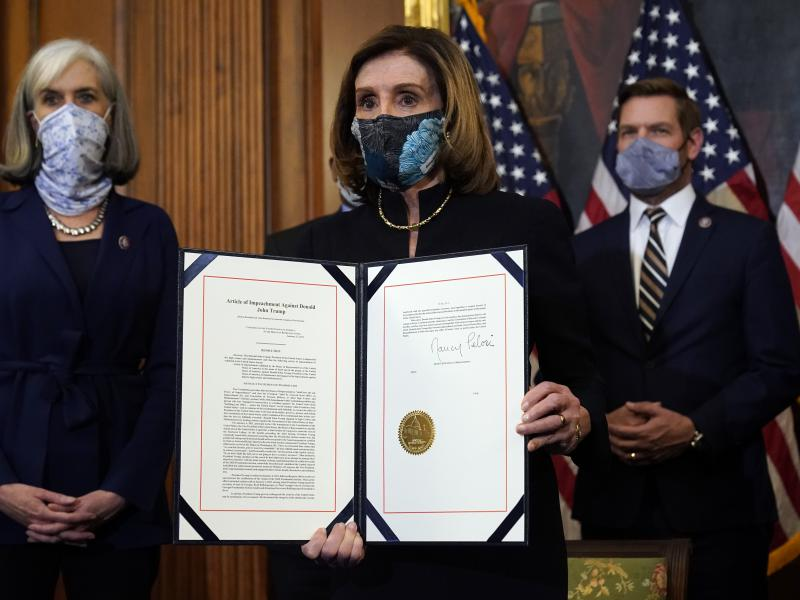 House Speaker Nancy Pelosi of Calif., displays the signed article of impeachment against President Donald Trump in an engrossment ceremony before transmission to the Senate for trial on Capitol Hill. It's unclear when a Senate trial will start
