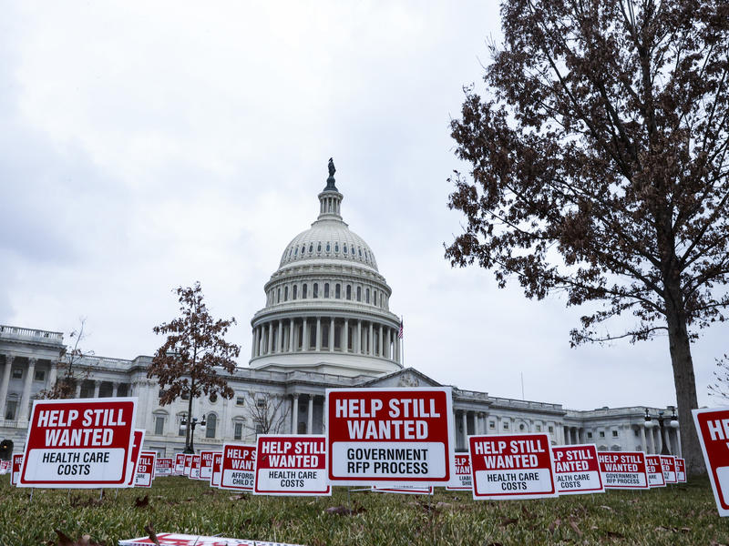 """Signs reading """"Help Still Wanted"""" were positioned on the lawn outside the U.S. Capitol on Jan. 5. The House Budget Committee meets Monday afternoon, setting up a vote on the coronavirus relief package by the end of the week."""