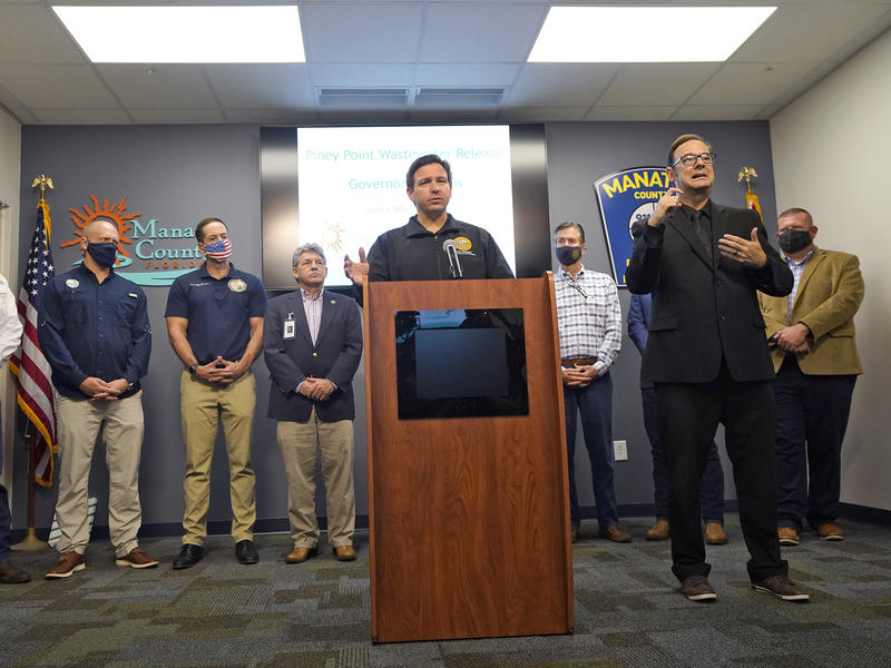 Florida Gov. Ron DeSantis gestures as he stands with state and local officials during a news conference Sunday at the Manatee County Emergency Management office in Palmetto, Fla.