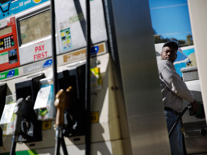 Motorist Jerry Reed watches the pump display while filling up his tank at a gas station, Thursday, Oct. 30, 2014, in Atlanta.