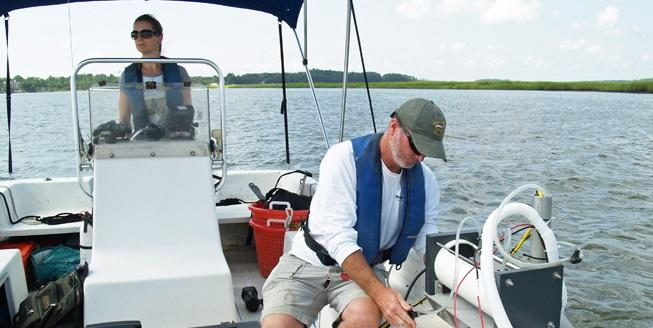 Researcher Mike Robinson with the UGA Skidaway Institute of Oceanography adjusts the salinity monitoring equipment while LeAnn DeLeo drives the boat.